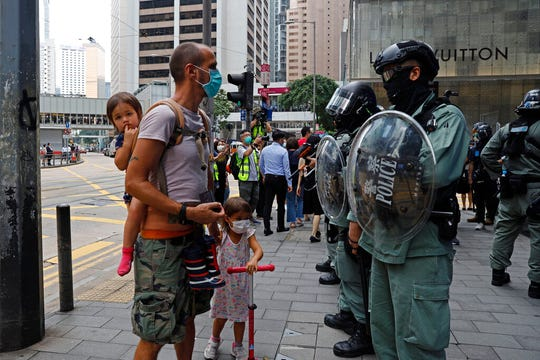 People cross as riot police stand guard during a protest in the Central district Hong Kong, Wednesday, May 27, 2020. U.S. Secretary of State of Mike Pompeo has notified Congress that the Trump administration no longer regards Hong Kong as autonomous from mainland China.