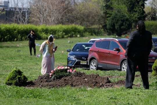 Family and friends watch from a distance or their cars as Erika Bermudez stands over her mother Eudiana Smith's grave after she was buried in Bayview Cemetery, Saturday, May 2, 2020 in Jersey City, N.J.
