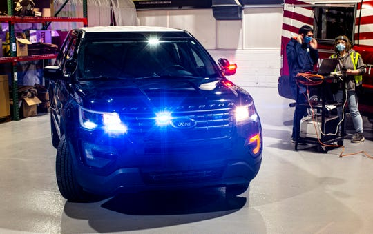 Flashing hazard and tail lights of Ford's Police Interceptor Utility vehicle warn officers that the high-temperature interior disinfecting process is running. The sanitation procedure seeks to limit the spread of COVID-19 to first responders.