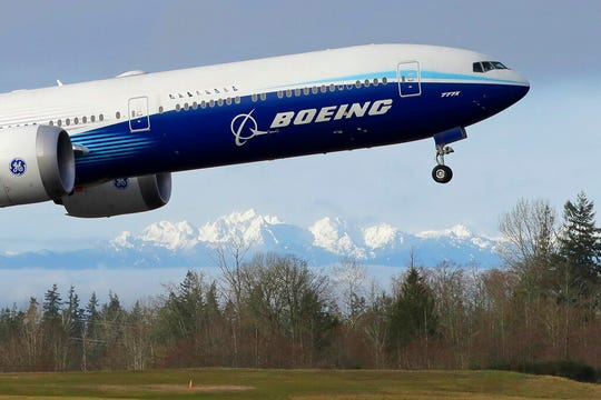 In this Jan. 25, 2020, file photo a Boeing 777X airplane takes off on its first flight with the Olympic Mountains in the background at Paine Field in Everett, Wash.  Boeing on Wednesday, May 27, is cutting more than 12,000 jobs through layoffs and buyouts as the coronavirus pandemic seizes the travel industry. And the aircraft maker says more cuts are coming.
