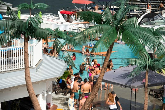 Crowds of people gather at Coconuts Caribbean Beach Bar & Grill in Gravois Mills, Missouri, Sunday, May 24, 2020.