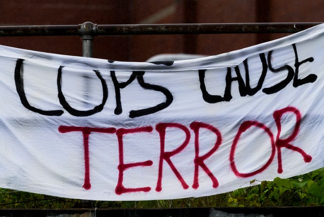 """A sign reading """"Cops cause terror"""" hangs off the railroad bridge above East Virginia Street in Evansville, Ind., Wednesday morning, May 27, 2020."""