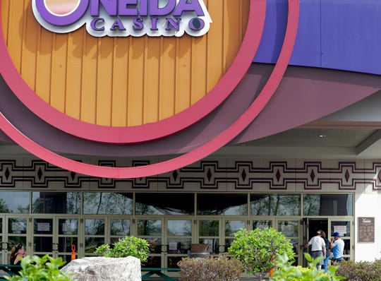 Gamblers sit outside and talk on the phone while others enter the building to play the machines on Wednesday, May 27, 2020, at Oneida Casino in  Ashwaubenon, Wisconsin. Once gamblers enter the door, their temperature is scanned.  Ebony Cox/USA TODAY NETWORK-Wisconsin
