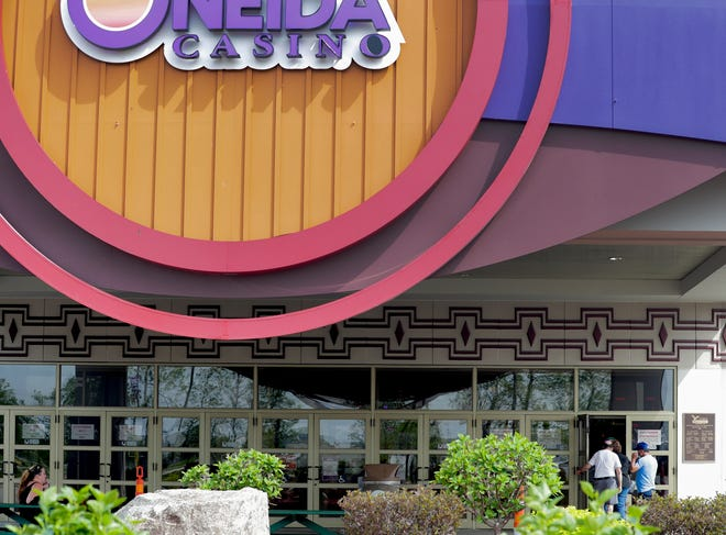 Gamblers sit outside and talk on the phone while others enter the building to play the machines  at Oneida Casino in  Ashwaubenon.