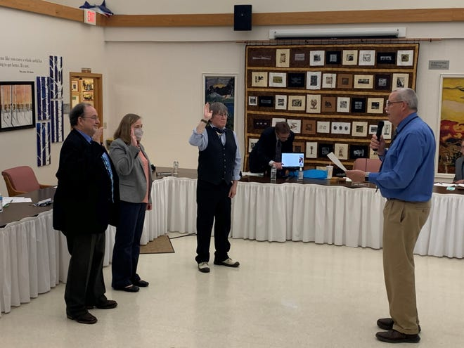 Newly elected trustees Jan Cahill (left), Kim Skornogoski and Bill Bronson, stand before Brian Patrick the district's Director of Business Operations while being sworn in.