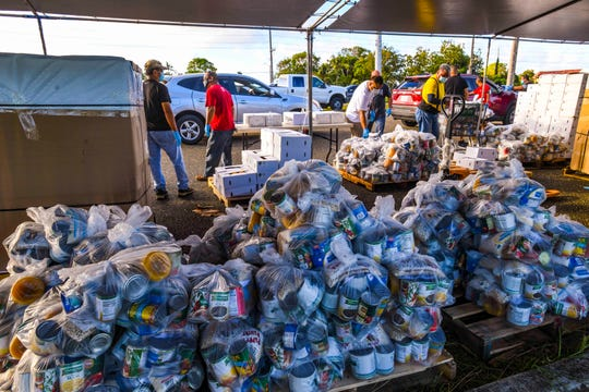 Guam Department of Education and Department of Public Works employees and others deliver Disaster Household Distribution food commodity bags to vehicles at the Tiyan Baseball Field in Barrigada in this May 27 file photo.