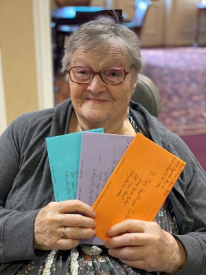 A St. Mary Healthcare Center resident holds up letters she received from Purdue students in Keith Molter's Customer Relations Management class.