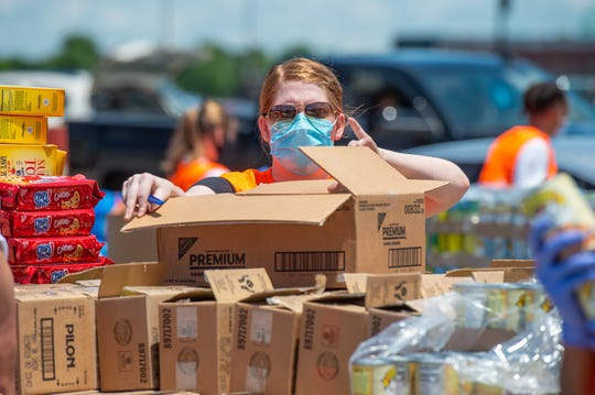 Logan Pearce along with Volunteers from United Way of Acadiana, Second Harvest Food Bankandthe University of Louisiana at Lafayette distribute food supplies at acontact-free, drive-thru food distribution for anyone experiencing economic hardship.Wednesday, May 27, 2020.