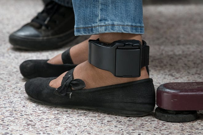 An ankle monitor is seen on a migrant woman from El Salvador, recently released from federal detention with fellow Central American asylum seekers, at a bus depot on June 12, 2019, in McAllen, Texas. (Photo by Loren ELLIOTT / AFP)