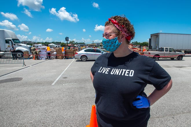Elsa Dimitriadis coordinating traffic at Cajun Field. Volunteers from United Way of Acadiana, Second Harvest Food Bankandthe University of Louisiana at Lafayette distribute food supplies at acontact-free, drive-thru food distribution for anyone experiencing economic hardship.Wednesday, May 27, 2020.