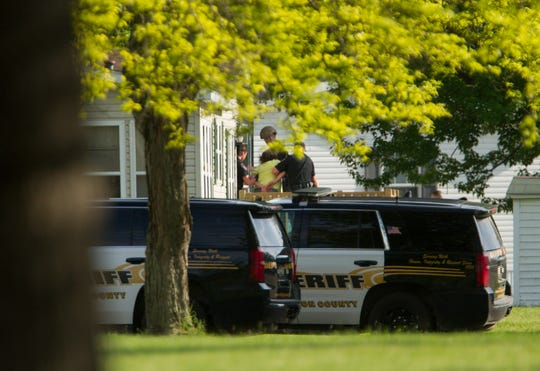 Livingston County Sheriff's office deputies lead a woman out of her home in Sylvan Glen in Genoa Township Wednesday, May 27, 2020 after several hours of deputies and Michigan State Police officers surrounding the home with guns.