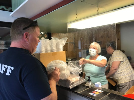 A customer stops by Cobblestone Confections, 343 Lexington Ave., on Wednesday to buy cups during the liquidation sale. Merry Birmelin, the owner, said the coronavirus has caused her to close the business.