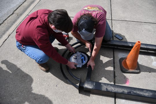 ASUMH Technical Center students Brady Hamm and Christian Hagaman affix the circular logo of the Mountain Home Entertainment District to a display sign on Thursday, May 21.