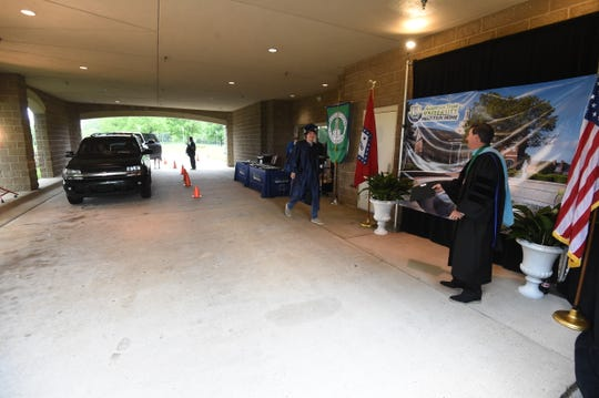 Dr. Robin Myers, Chancellor of ASUMH waits under the school's portico Wednesday to take a photo with the first student to participate in the school's drive-thru graduation ceremony.