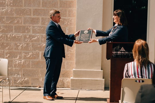 Chris Broadwater, acting chancellor for Louisiana Delta Community College,  accepts a plaque from 4th Judicial District Court Judge Sharon Marchman honoring the organization's role in educating drug court participants.