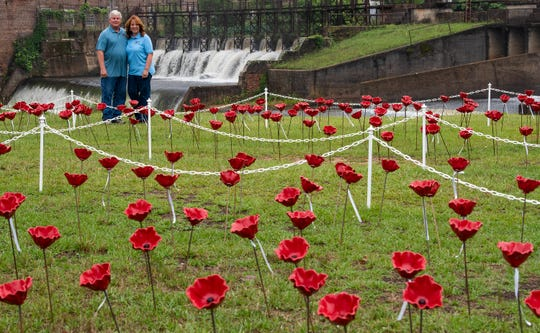Steven Hansen and Julianne Hansen stand among 1,001 ceramic poppies that are are on display for Memorial Day week in downtown Prattville, Ala., on Wednesday May 27, 2020, as part of the Alabama Poppy Project. The flowers have ribbons attached that show veterans names who were killed in wars or are no longer with us.