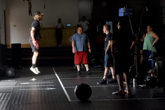 Steele Strout leads a class Wednesday at CrossFit Veneration in Johnstown. Members now must pre-register for the 16-personclasses, and rectangles have been taped off to give attendees their own designated workout space.