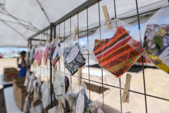 Masks are displayed inside plastic bags for sale by Hawks Audio Works and Kustoms in a tent on a rented lot across the street from Jake's Cafe in Las Cruces on Wednesday, May 27, 2020.