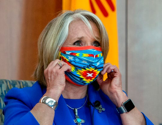 New Mexico Gov. Michelle Lujan Grisham removes her face mask at the start of an update on the COVID-19 outbreak in New Mexico and the state's effort to limit the impact of the disease on residents, during a news conference at the State Capitol in Santa Fe, N.M., Wednesday May 27, 2020.