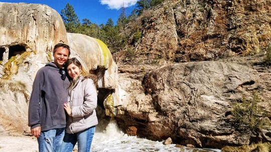 Sun-News reporter Jacqueline Devine stands with her husband Anthony Milana in front of the Soda Dam situated along the east side of New Mexico State Route 4, just north of the Village of Jemez Springs.