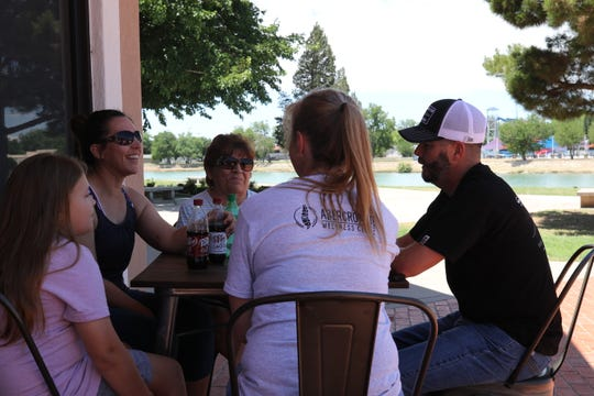 Kristi Naylor (center) and her family enjoy a cold drink outside PJ and B's Rio Cafe, May 27, 2020 in Carlsbad.