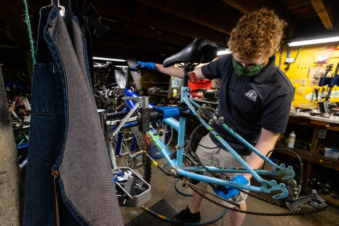 John Eppley, Alpine Cycles general manager, works on repairing a customer's bicycle Wednesday, May 27, 2020, in the store's workshop. Alpine Cycles staff will be doing free bike checkups that include filling tires, checking chains and inspecting brakes at local parks in June and July.