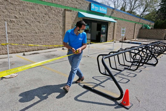 Habitat Humanity Lakestore ReStore Operations Manager Jared Beckman, stretches out caution tape, Wednesday, May 27, 2020, at the entrance of the ReStore facility.  Beckman said that the store will open with a 10 person limit.  He added that he expects that to be expanded fairly soon.