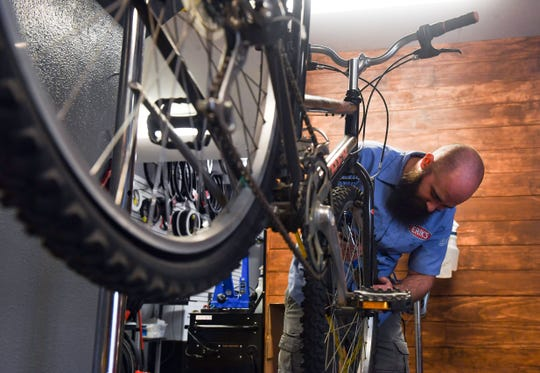 Peter Wimmer puts air in a customer's bike tire to check for a leak on Wednesday, May 27, at Erik's Bike Shop in Sioux Falls.