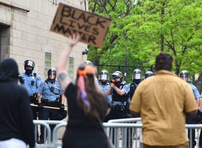 People hold signs in front of the Minneapolis Police Department&#39;s Third Precinct headquarters building as police form a line Wednesday, May 27, 2020, in Minneapolis, Minn.<em> (Dave Schwarz/St. Cloud Times)</em>