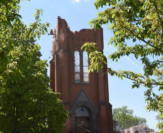 Debris falls from St. Mary's Catholic Church as it continues to be demolished Wednesday, May 27, 2020, in Melrose.