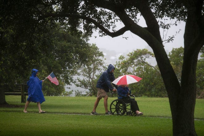 """Julie Biron (from left), Todd Biron, and Sandra Rick, all of Vero Beach, place flags on the memorials at Veterans Memorial Island Sanctuary on a rainy Memorial Day,  May 25, 2020, in Vero Beach. """"Rain? This is the least I can do. They sacrificed their lives,"""" Todd Biron said. The group was remembering Rick's husband and Julie Biron's father, who died in 2019, He was in the Army and served on the color guard."""
