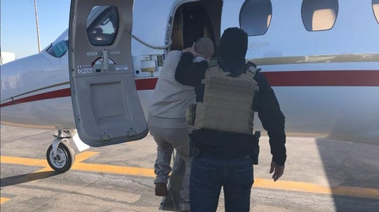 """El Iraqui"" Jose Dolores Villegas Soto, a reputed Juarez gang leader, is escorted onto a plane to be taken to a prison in southern Mexico."