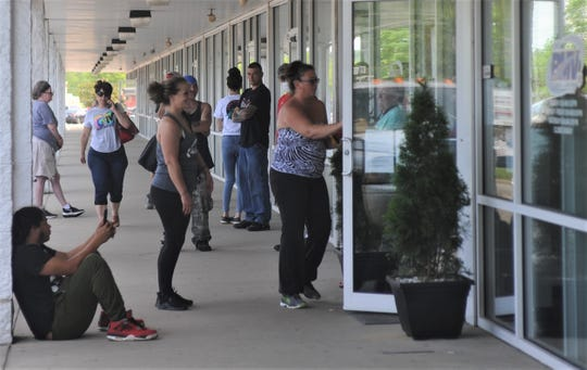 People wait outside of the Bureau of Motor Vehicles (BMV) in Zanesville on Wednesday. The office opened on Tuesday, and people must wait outside due to limited capacity to meet social distancing guidelines.