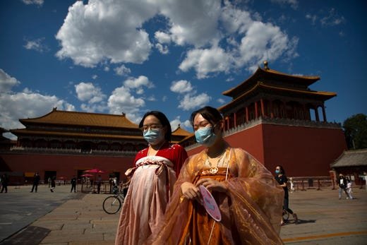 Women in period dress and wearing face masks to protect against the new coronavirus walk outside the entrance to the Forbidden City in Beijing, Wednesday, May 27, 2020. The Chinese People's Political Consultative Conference concluded its session in Beijing on Wednesday, part of the annual meetings of China's two top legislative bodies.