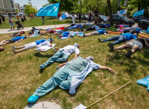 Healthcare workers demanding time off for COVID-19 fatigue stage a lie-in in front of Maisonneuve Rosemont hospital, Wednesday May 27, 2020, in Montreal.