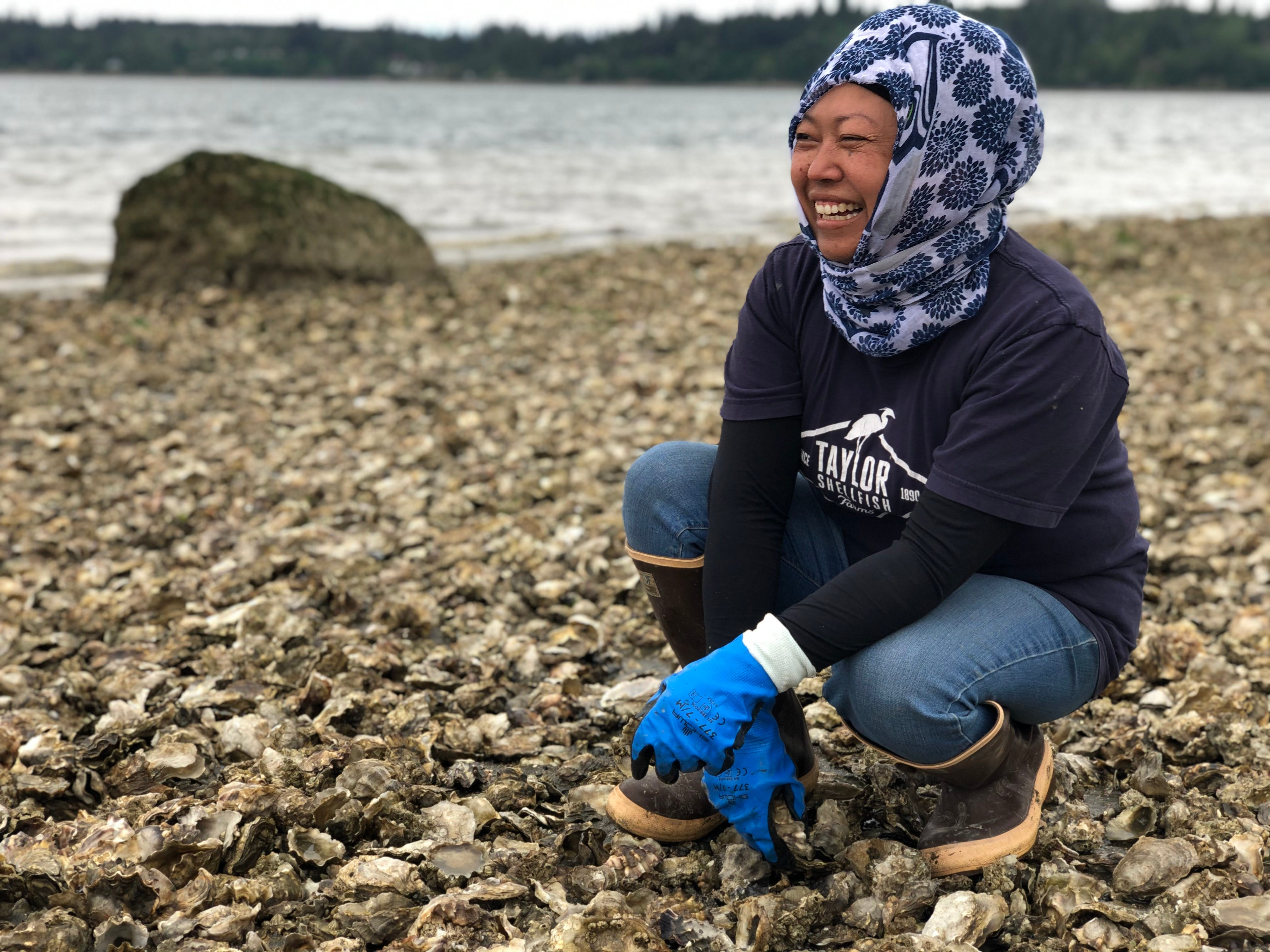 Aisha Prohim, looks for oysters on the eastern shore of the Totten Inlet near Olympia, Wash., on May 11, 2020.