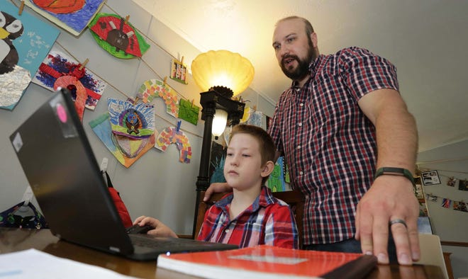 Eli Bartell, 8, left, works on homework at the kitchen table as his dad Andrew gives him guidance last week in Sheboygan.