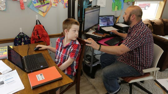 Eli Bartell, 8, turns around to ask his dad, Andy, a question while working on his studies at home last week in Sheboygan.