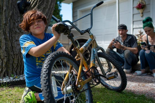 Emilio Ortiz-Laclair, 9, stops by his mother's friend's house after a bike ride on Thursday, May 21, 2020 in Breckenridge, Mich.