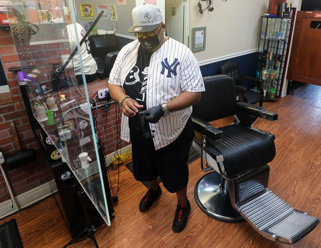 Reuben Wilkins dons a pair of gloves at his Barber Lounge on Pacific Avenue in Bremerton on Thursday.