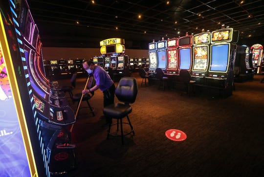 Julian Opido, a member of the housekeeping staff, sweeps off the bottom of the slot machines Wednesday as employees prepare for the reopening of the Point Casino on June 1.