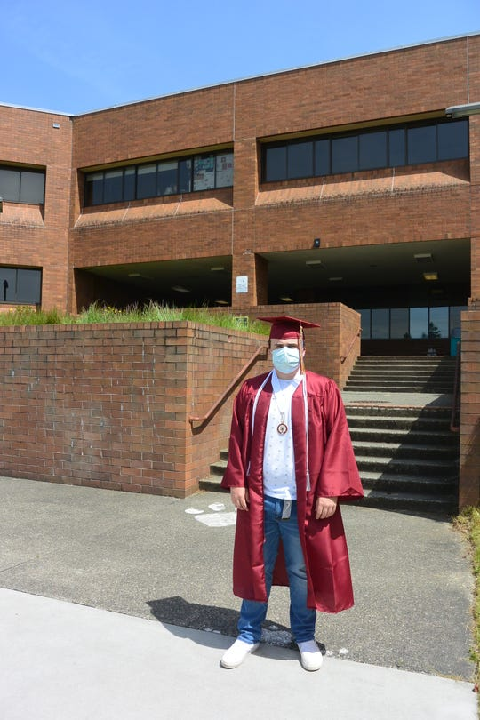 Gabe Winn, a South Kitsap High School senior in the Class of 2020, stands in front of the school wearing his cap and gown and a mask.