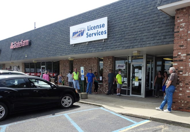 People wait outside the Coshocton County Bureau of Motor Vehicles about noon on Wednesday in Downtowner Plaza. People in line were reporting about 15 to 20 minutes outside the building. Some were waiting on those inside conducting business. Based on state guidelines, DMV buildings that reopened on Tuesday could only have half capacity inside and had to recognize cleaning and safety precautions, like social distancing.