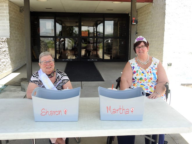 Sharon Burns and Martha Richardson sit outside Hopewell School on Wednesday, awaiting a drive-thru card shower for their retirements. Burns was given a sash and Richardson a tiara to mark the occasion. People places cards in the two baskets for them.