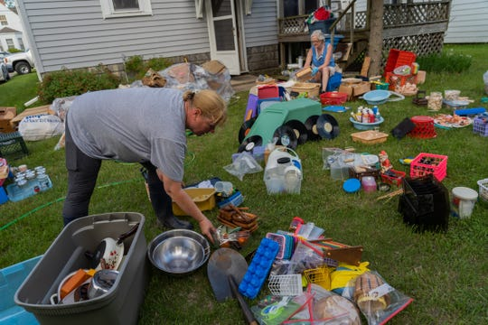 Avis Crowley (right) of East Tawas helps Andrea Skrocki of Bay City clean items from her basement that were involved in flooding that went through the area on Wednesday, May 27, 2020 in Tawas City.