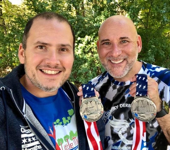Tommy Craft, left, and Marcus Carmicle, with their medals from the half-marathon from the 2019 Free Press marathon.