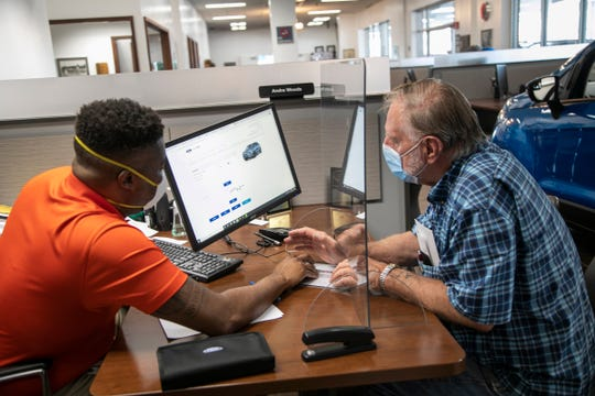Sales consultant Andre Woods, left, helps Al Janowski, 81, on Wednesday with paperwork for his 2020 F-150 lease at Village Ford in Dearborn. New social distancing norms have a sneeze guard at Woods' work station. Car dealerships in Michigan can now open their showrooms to customers by appointment only.