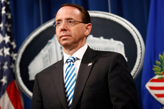 FILE - In this April 18, 2019 file photo, then Deputy Attorney General Rod Rosenstein listens as Attorney General William Barr speaks about the release of a redacted version of special counsel Robert Mueller's report during a news conference at the Department of Justice in Washington.