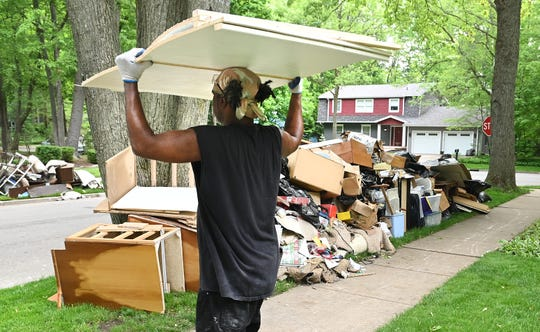 Albert Henderson of SERVPRO removes flood-damaged debris from the home of Richard Rasmussen in Midland.