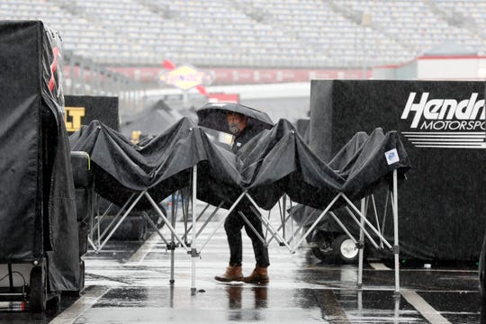 A man walks through the infield as rain falls before a NASCAR Cup Series auto race at Charlotte Motor Speedway Wednesday, May 27, 2020, in Concord, N.C.